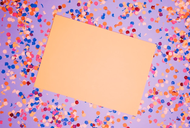 Elevated view of blank paper over colorful confetti against purple backdrop