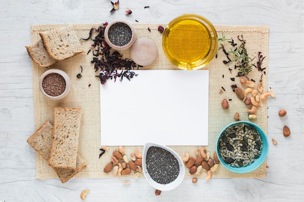 Elevated view of blank paper surrounded by healthy food over placemat on table