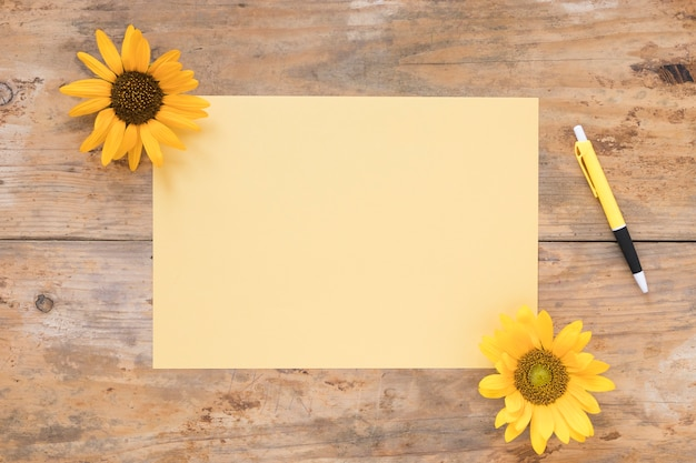 Elevated view of blank paper with yellow sunflowers and pen on wooden backdrop