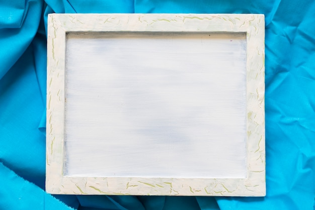 Elevated view of blank picture frame on blue textile