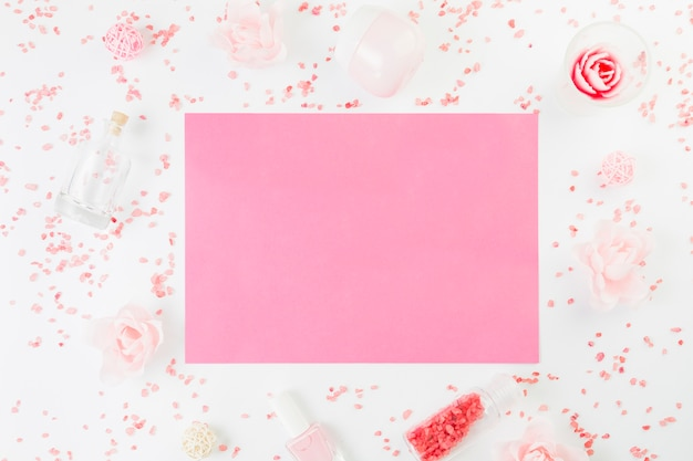 Elevated view of blank pink paper surrounded with beauty products on white surface