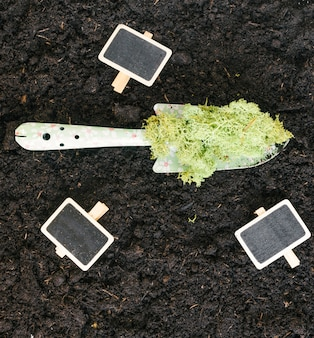Elevated view of blank slate; moss on shovel over black dirt