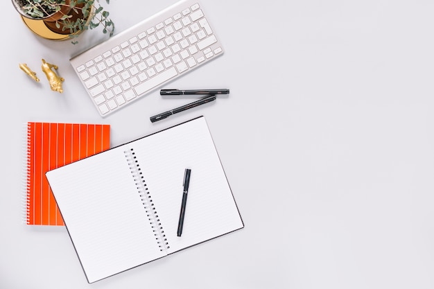 Elevated view of blank spiral diary; pen; keyboard and golden animal miniature statue on white background