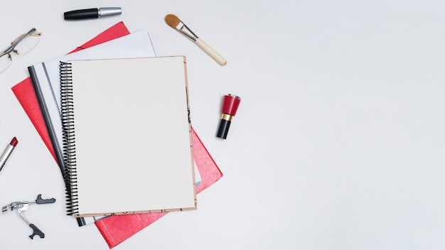 Elevated view of blank spiral notebook surrounded by nail varnish; makeup brush; mascara; eyeglass; lipstick; and eyelash curler over white background