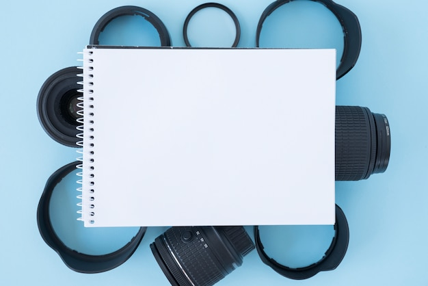 Elevated view of blank spiral notepad over camera accessories on blue background