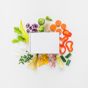 Elevated view of blank spiral notepad on fresh vegetables over white background