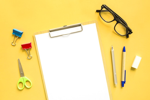 Elevated view of blank white paper near stationeries on yellow background