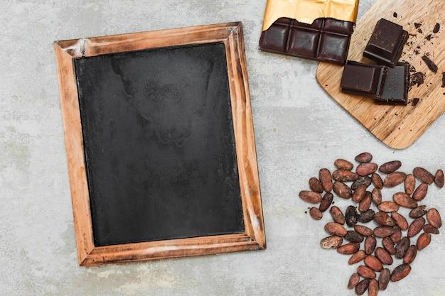 Vista elevata dell'ardesia di legno in bianco, della barra di cioccolato fondente e delle fave di cacao su fondo concreto