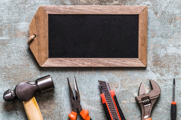 Elevated view of blank wooden tag and various worktools on old wooden background