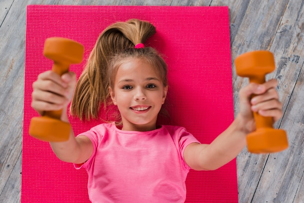 An elevated view of a blonde girl lying on pink carpet exercising with dumbbell
