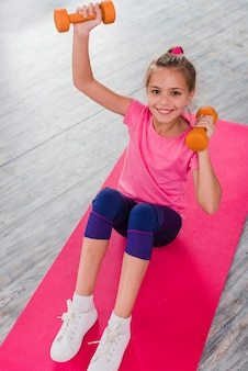 An elevated view of a blonde girl sitting on pink carpet exercising with dumbbell