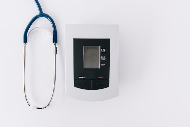Elevated view of blood pressure monitor and stethoscope on white backdrop