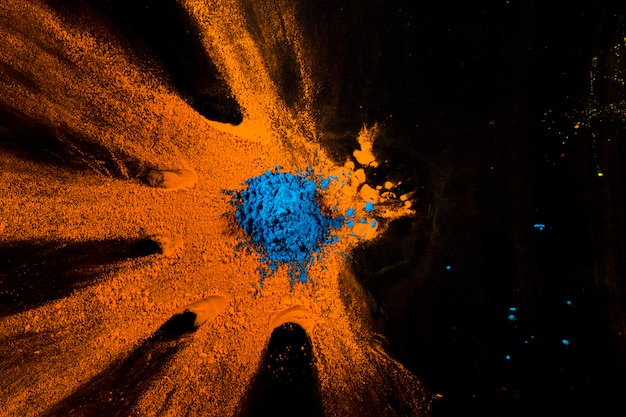 Elevated view of blue and orange powder on black surface