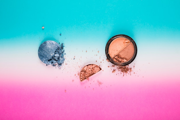 Elevated view of blusher and grey powder ball on colorful background