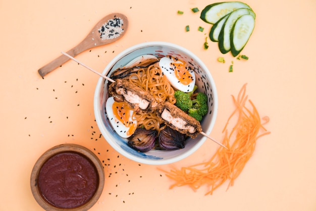 An elevated view of bowls with noodles; sauce; cucumber; carrot and sesame seeds on colored backdrop