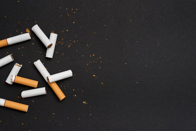 Elevated view of broken cigarette over black background