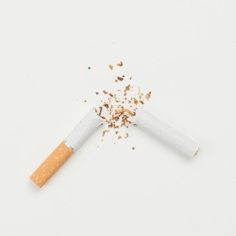 Elevated view of broken cigarette on white backdrop