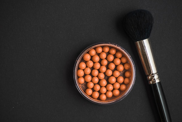 Elevated view of bronzing pearls and makeup brush on black surface