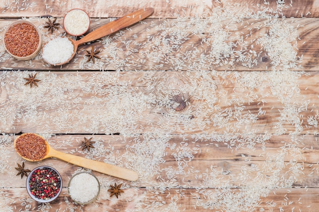 Elevated view of brown and white rice with dry spices arranged over weathered wooden texture background