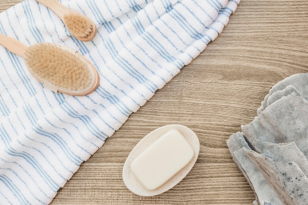 Elevated view of brush; towel; soap and sponge on wooden backdrop