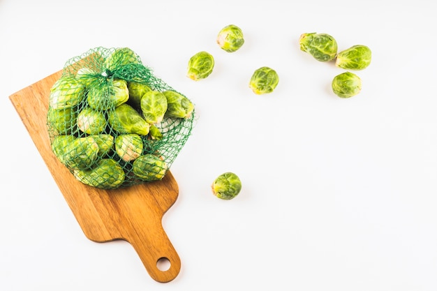 Elevated view of brussels sprouts in net on wooden chopping board