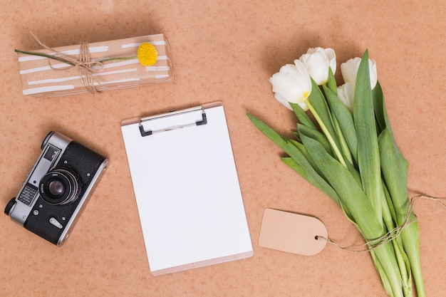 Elevated view of bunch of white tulip flowers; retro camera; gift box and white paper with clipboard on desk