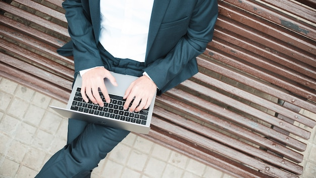 An elevated view of a businessman sitting on bench using laptop
