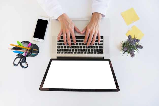 Elevated view of a businessperson's hand using laptop on desk