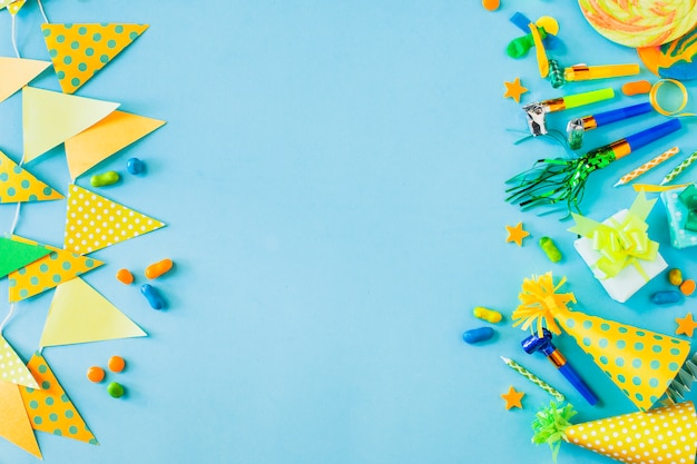 Elevated view of candies with party accessories on blue backdrop