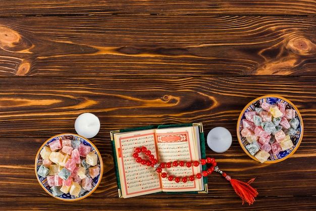 An elevated view of candles; red prayer beads with holy kuran and lukum bowls on wooden table