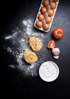 Elevated view of capellini pasta with egg carton; juicy tomato; garlic and bowl of flour over counter