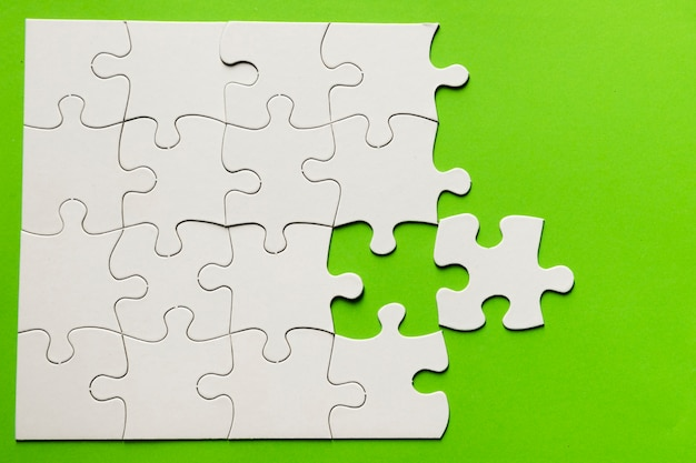 Elevated view of cardboard puzzle on green background
