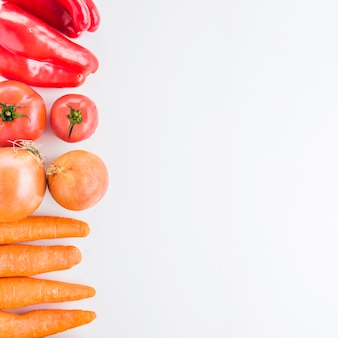 Elevated view of carrots; onions; tomatoes and red bell pepper on white background