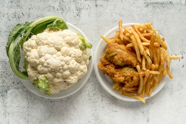 Elevated view of cauliflower and fried food over concrete background