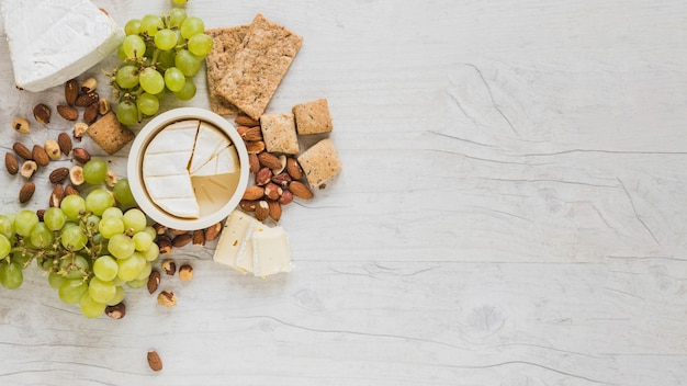 An elevated view of cheese cubes, grapes, dried fruits and crackers on grey wooden desk