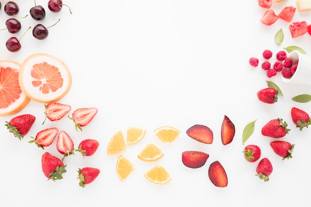 An elevated view of cherries; grapefruit; strawberries; lemon; plums; strawberries; watermelon and raspberries on white backdrop