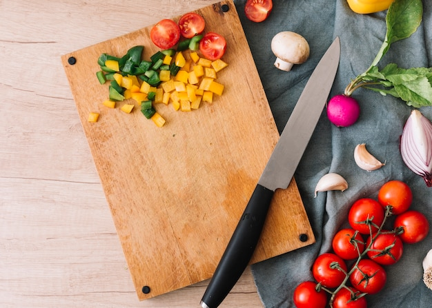 An elevated view of chopped vegetables on chopping board with knife over the table