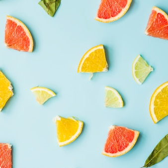 Elevated view of citrus fruit slices on blue background