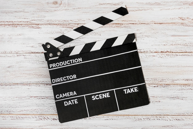 An elevated view on clapperboard over white wooden desk