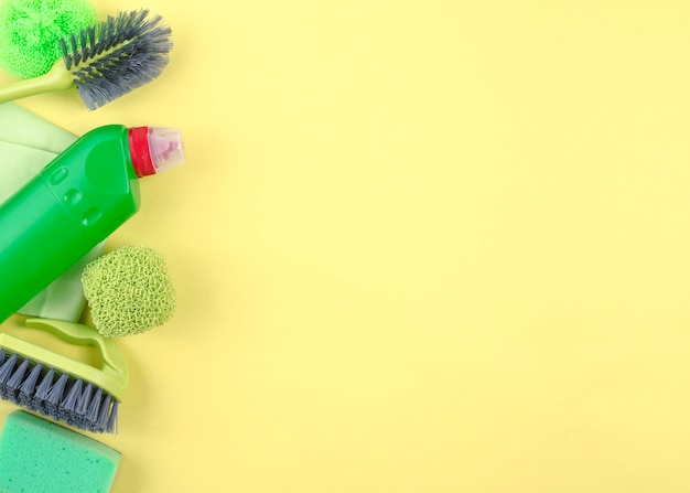 Elevated view of cleaning equipments on yellow background