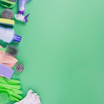 Elevated view of cleaning products on green background
