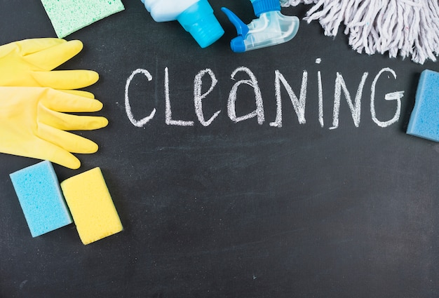 Elevated view of cleaning text with equipments on black background
