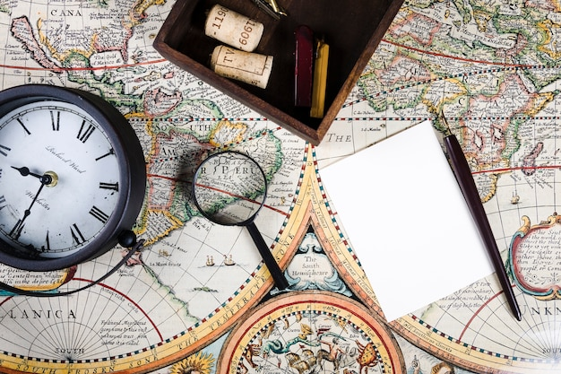 Elevated view of clock and magnifying glass on colorful ancient map