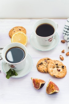Elevated view of coffee; backed cookies; almond; fig and lemon on wooden table