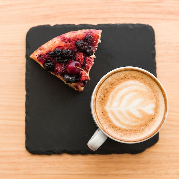Elevated view of coffee and berry pastry on wooden table