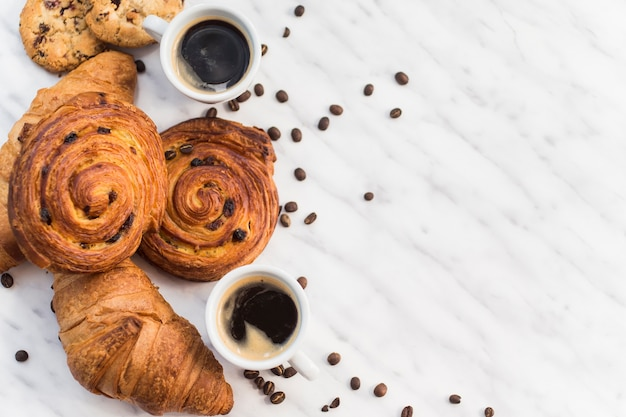 Elevated view of coffee and croissant with coffee bean on marble floor