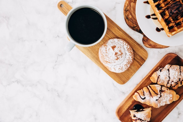 An elevated view of coffee cup; baked buns; croissant and waffles on wooden tray against marble textured background