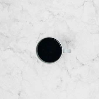 An elevated view of coffee cup over the marble textured backdrop