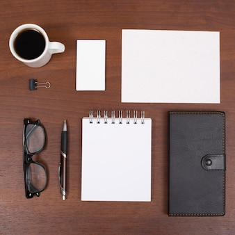 Elevated view of coffee cup and office stationery on wooden desk