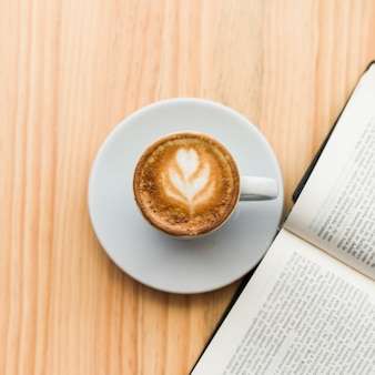 Elevated view of coffee latte and open book on wooden background